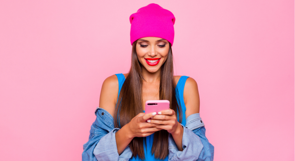 young woman wearing pink wooden hat, blue vest and denim off shoulder jacket, looking at phone she is holding whilst texting
