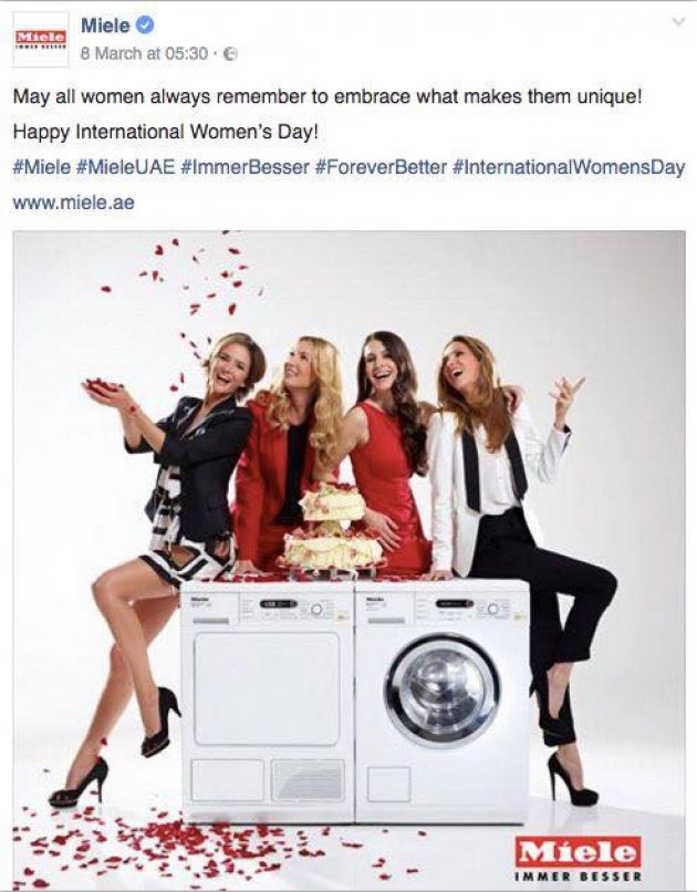 four women sitting on a tumble dryer and washing machine
